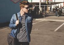 A young man walking through a parking lot carrying a computer bag