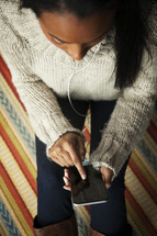 a young woman listening to music on a cellphone with earbuds