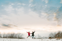 a couple jumping outdoors in snow
