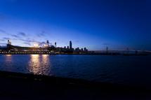 stadium lights at night across a river bay bridge san francisco att park