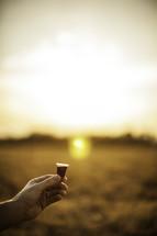 outside communion - hand holding communion wine