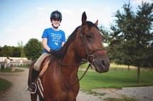 a teen girl riding a horse