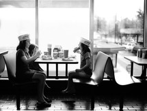 children eating hotdogs in a restaurant
