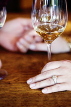 engagement ring and a wine glass