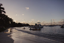 anchored boats and tide washing onto a shore at sunset