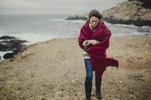 woman walking on a beach wrapped in a red blanket