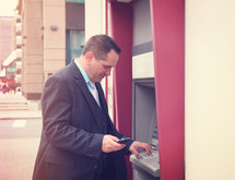 businessman at an ATM in a city