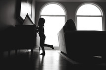 silhouette of a child in a living room