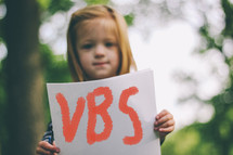 """Child holding a handwritten sign saying """"VBS."""""""