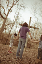 Mother and children holding hands before a wooden cross.