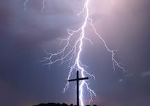 lightning striking behind a cross