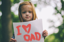 """I love Dad"" sign held by a child."