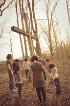 holding hands in prayer around a cross outdoors