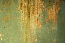 Green paint flaking off clay wall.