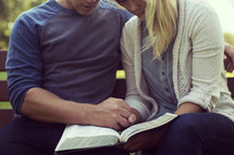 a couple reading a Bible together while sitting on a park bench