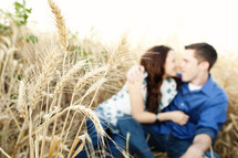 Happy couple outdoors in. A wheat field sitting embracing