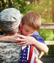 a boy hugging his soldier father