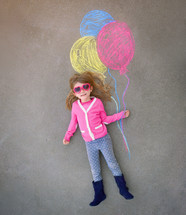 a little girl in sunglasses holding sidewalk chalk balloons