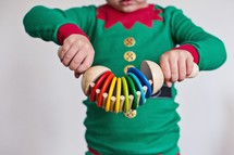 kid playing with toys in elf pajamas