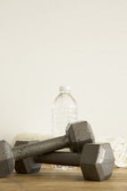 barbells, bottled water, and towel at the gym