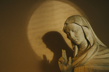 statue of Mary with two fingers raised to heaven