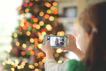 child taking a picture with a cellphone of a Christmas tree