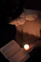woman reading a Bible by candle light