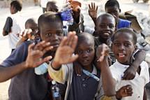 Group of children waving.