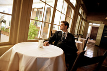 A groom sitting at a table looking out the window