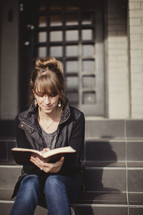 woman sitting on stairs reading a Bible