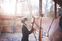 teen girl with her horse in a stable