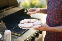man putting hamburgers on the grill