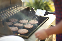 a man cooking hamburgers on the grill