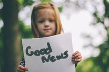 Girl holding Good News sign