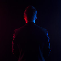 Man in suit facing away with red and blue lights.