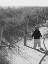 a curious toddler boy exploring a sand dune