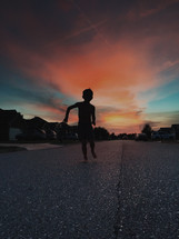 silhouette of a child running down a neighborhood street at dusk
