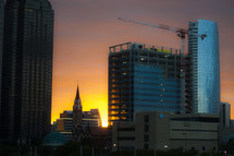 construction crane on a skyscraper at sunset