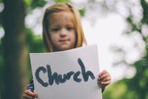 """Little girl holding a handwritten sign saying """"church."""""""