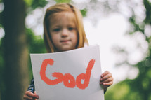 "A child holding a handwritten sign saying, ""God."""