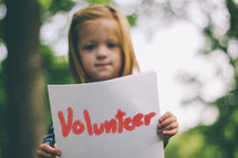 girl holding volunteer sign