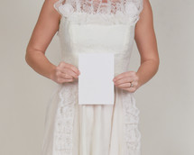 a bride holding a blank piece of white paper