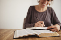 woman reading in a Bible and writing in a journal