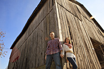 A couple holding hands standing by a barn