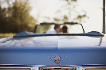 A couple kisses while sitting in a blue cadillac convertible