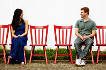 man and woman sitting in red chairs