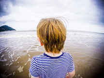a boy child standing with his feet in the water at a beach