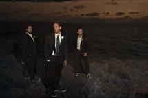 groomsmen standing on rocks in front of water