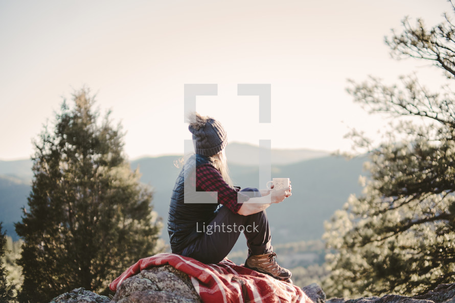 a woman sitting on a blanket on a rock drinking coffee