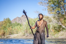 John the Baptist with a staff in the wilderness ready to baptize and prepare the way for the coming King. Voice of calling in the wilderness. Dedicated disciple and biblical character follower of jesus
